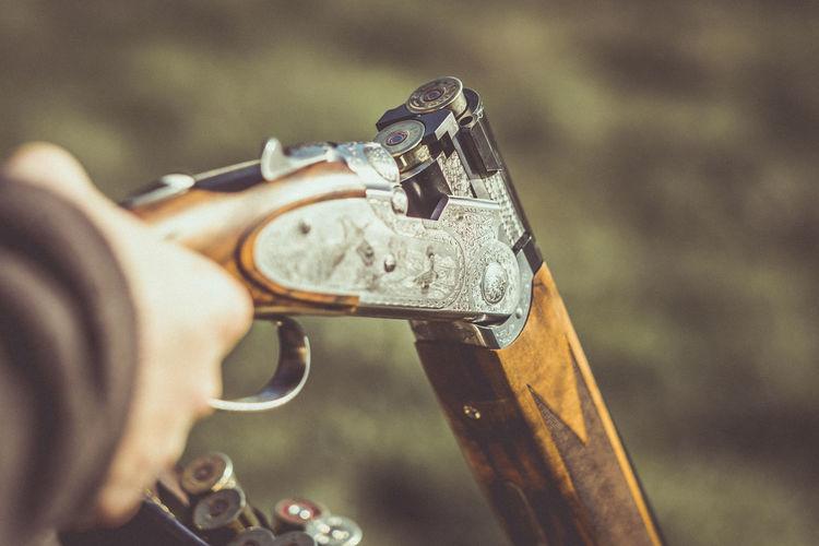 Cropped Image Of Man Holding Shotgun