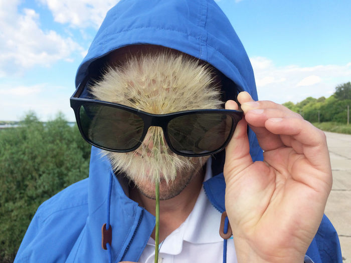 Man wearing sunglasses while covering face with dandelion