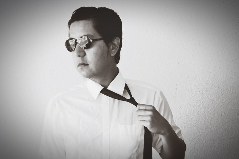 Man in sunglasses removing necktie against wall