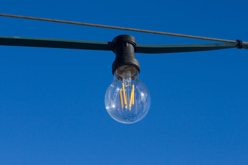 Blue Light Bulb Lighting Equipment Clear Sky Low Angle View Electricity  Sky Hanging No People Nature Close-up Single Object Cable Outdoors Fuel And Power Generation Transparent Bulb Day Copy Space Light Power Supply Electrical Equipment Blue Background