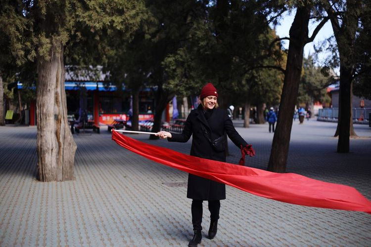Smiling young woman with red fabric while walking on street during winter