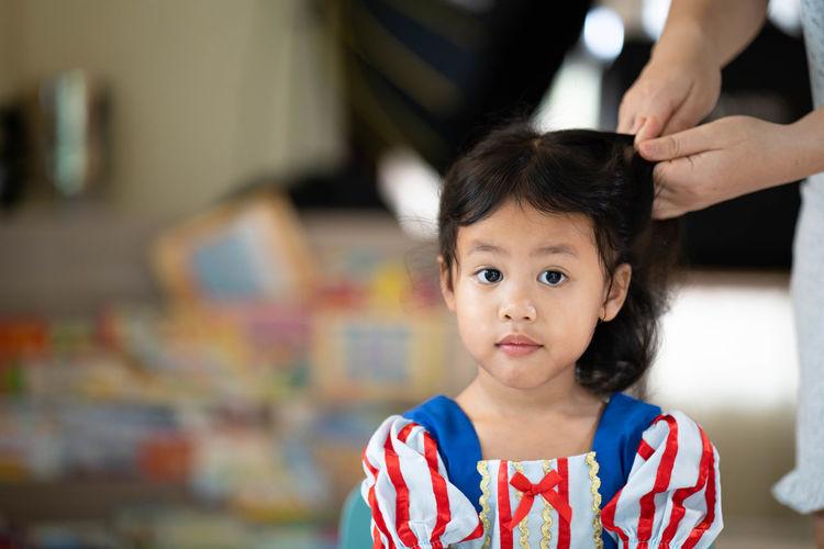 mother is braiding her daughter hair indoor