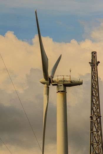Low angle view of windmill and electricity pylon against sky