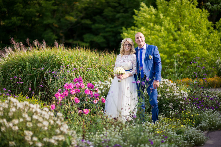 Portrait of bridal couple standing amidst flowers blooming at park