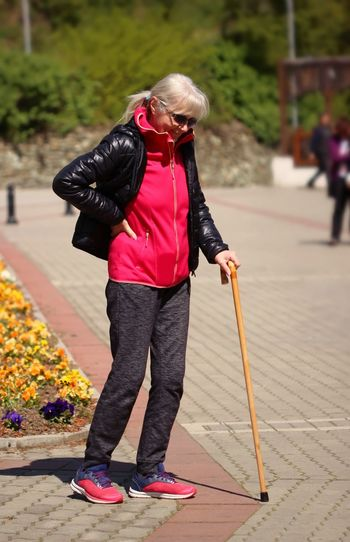 Full length of senior woman with walking cane on footpath at park
