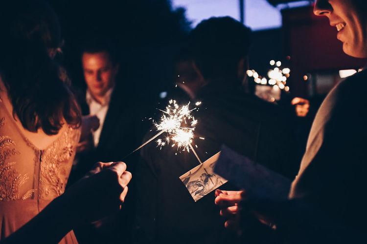 Group of people watching firework display at night