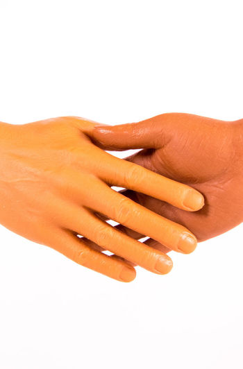 Close-up of hand touching finger against white background