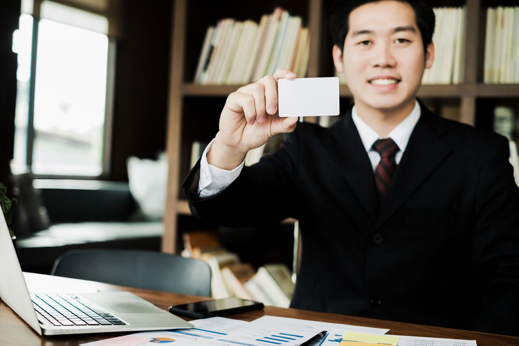 Portrait Of Businessman Holding Blank Card While Sitting In Office