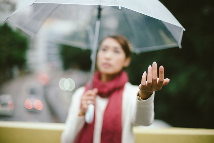 Young woman with umbrella standing outdoors during rainy season