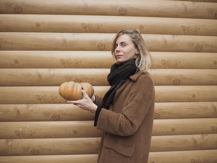 Side view of woman holding pumpkin while standing by wooden wall