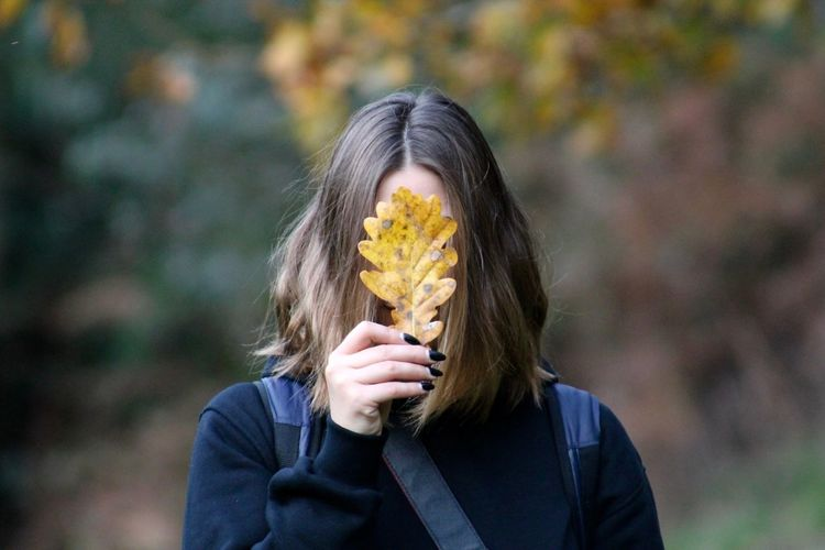 Woman Holding Autumn Leaf In Front Of Face