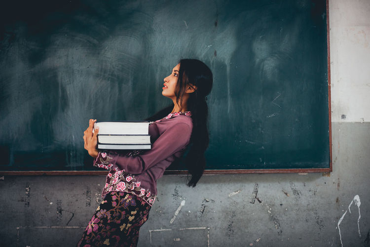 Side View Of Teacher Carrying Books While Walking By Blackboard In Classroom