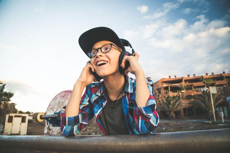 Smiling Boy Listening Music Through Headphones Against Sky
