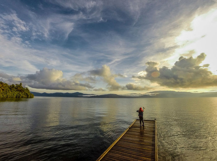 Rear view of woman standing by lake on pier during sunset