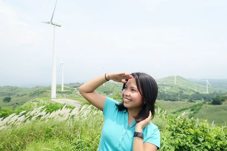 Smiling young woman shielding eyes while looking away against windmills and sky on field