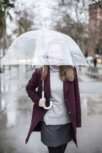 Woman with umbrella walking in city