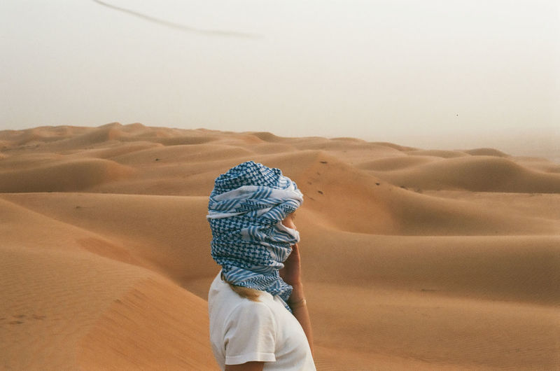 Mid adult woman wearing headscarf on desert against sky