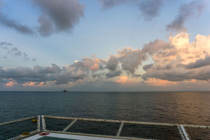 seascape oil field from a helideck Construction Barge Ocean Cloudy Oil Field Petroleum Offshore Offshore Life Platfrom Helideck Heliport Net Deck Evening Water Sea Beach Sunset Sand Backgrounds Nautical Vessel Summer Blue Sky Seascape Wave Horizon Over Water