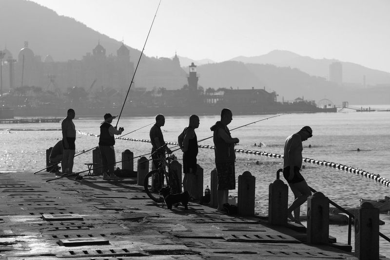 Early morning fishermen and swimmers at Xinghai Bay, Dalian, China. Blackandwhite China Dal Early Morning Fishermen Fishing Men Morning Outdoors Sea Silhouette Swimming Tranquility Water Xinghai Xinghai Bay