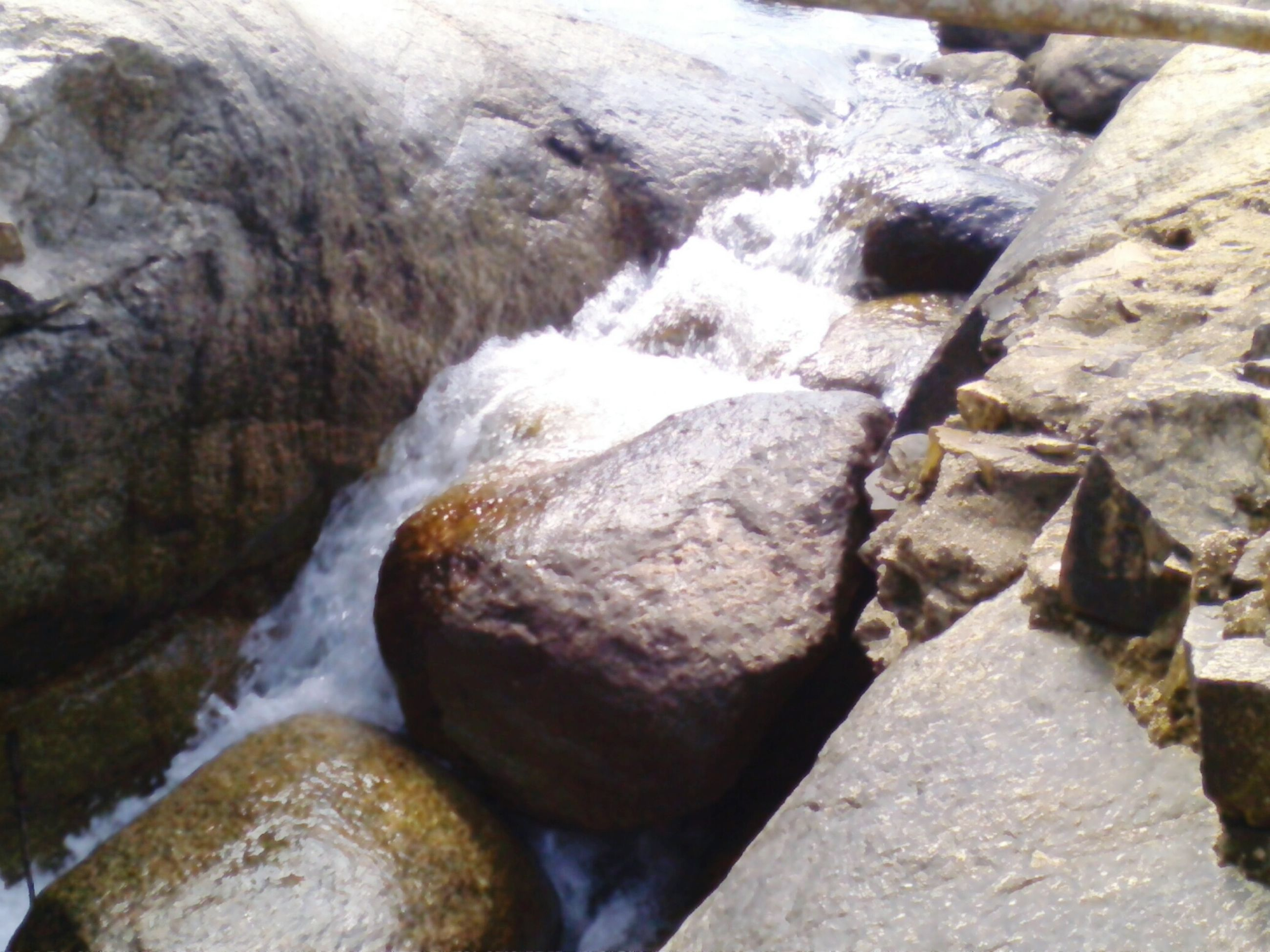 rock - object, water, flowing water, motion, nature, rock, stone - object, flowing, rock formation, beauty in nature, stone, day, waterfall, outdoors, stream, surf, textured, no people, close-up, splashing
