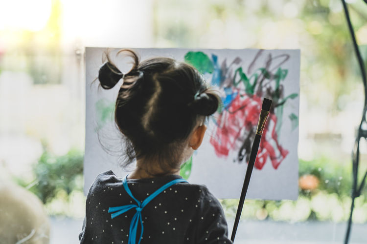 Rear view of girl painting on paper