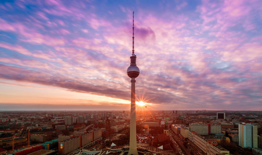 Communications Tower In City Against Cloudy Sky At Sunset