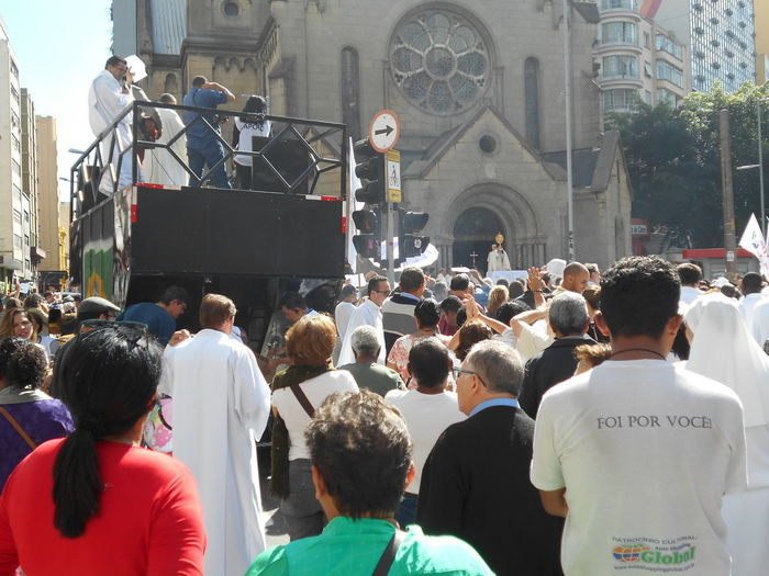 """""""Foi por Você."""" - """"I did this for you."""" The backside of the white T-shirt in this photo says, in Portuguese """"Foi por você."""" which translates, in English, to: """"I did this for you."""" This group of people have gathered together for an outdoor mass held in front of the Santa Ifigênia church in downtown São Paulo, commemorating the Corpus Christi holiday May 31st. The size of the crowd reflects the deep faith of the people. In Brazil, Corpus Christi is a Catholic celebration commemorating the Eucharist (the Eucharist is the symbolic presence of the Body of Christ in the consecrated host). Hence, the saying """"Foi por você."""" is in reference to Christ having died in your name; he died for you. The Corpus Christi holiday does not happen on the same day every year. Corpus Christi Corpus Christi Holiday Igreja Santa Ifigênia Igreja De Santa Ifigênia May 31 May 31, 2018 Passion Of Christ Santa Ifigenia Viaduct Susan A. Case Sabir Unretouched Photography Belief Catholic Faith Catholic Religion Downtown São Paulo Large Group Of People Outdoor Mass Outdoor Congregation Real People Reinforcement Santa Ifigenia Solidarity Street Photography Sunny Day Togetherness Urban Photography"""