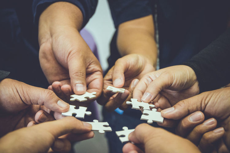 Cropped Hands Of People Holding Jigsaw Puzzle