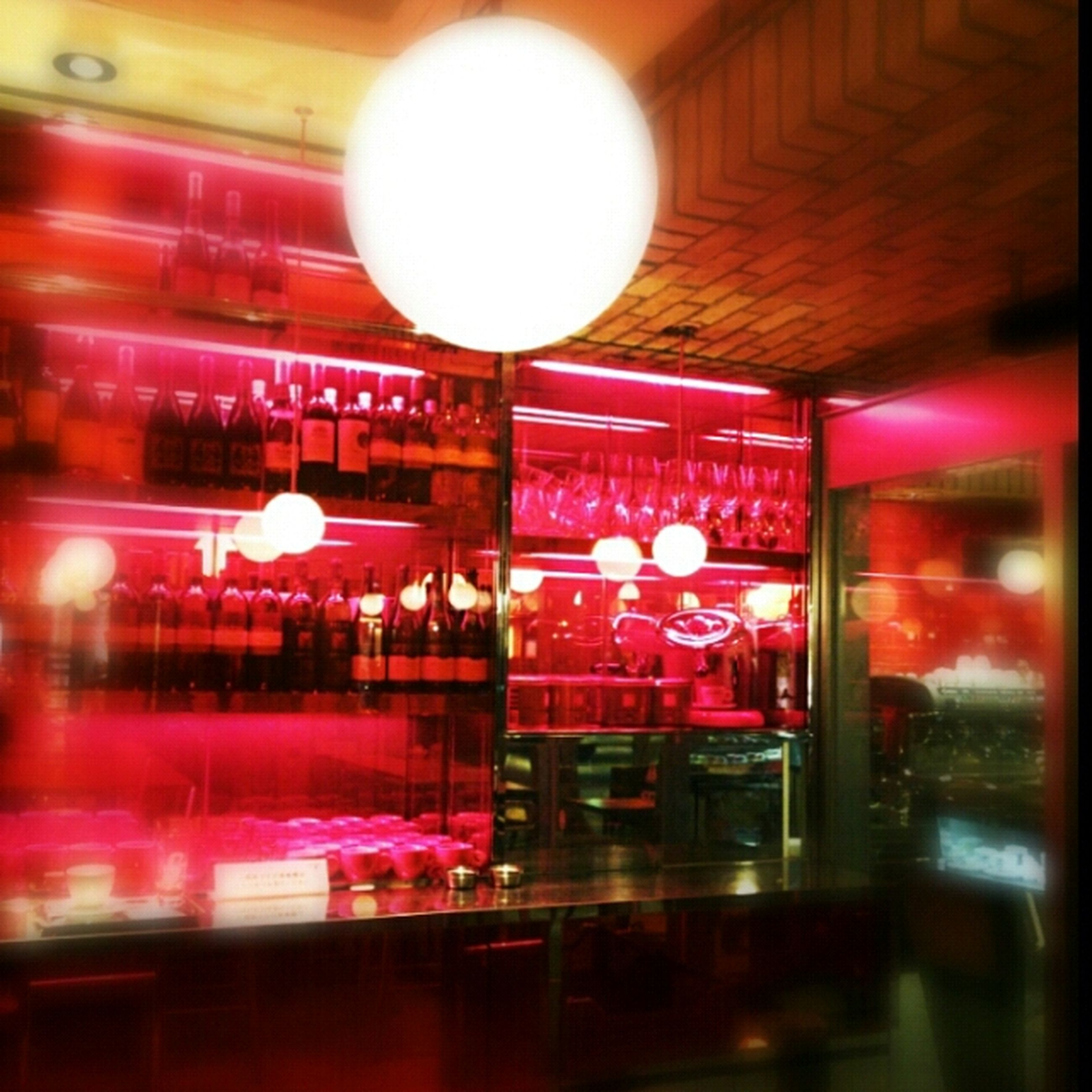 indoors, illuminated, night, glass - material, restaurant, lighting equipment, store, reflection, transparent, table, window, retail, incidental people, food and drink, celebration, red, hanging, shop, display, built structure