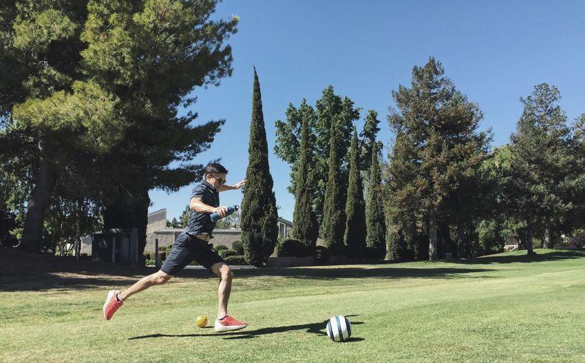 Full length of man kicking soccer ball at park
