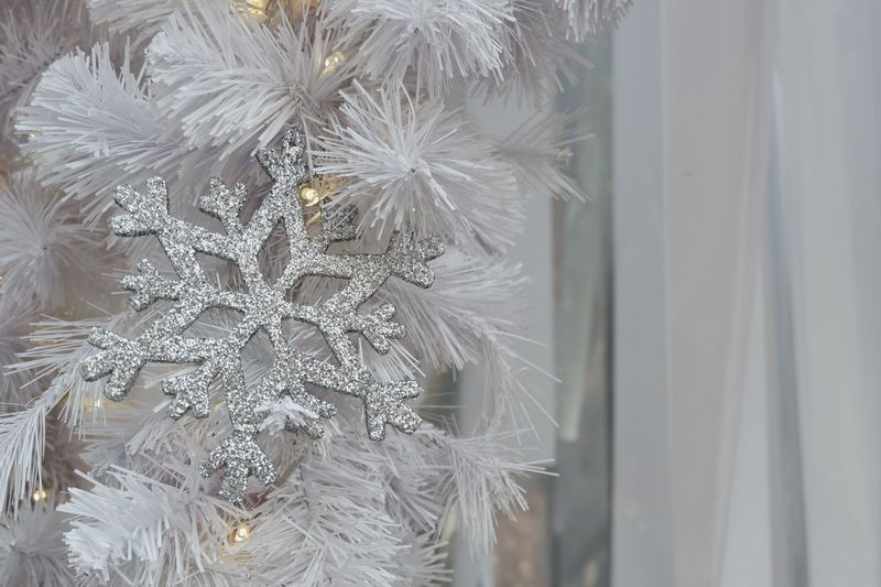 Sparkling silver snowflake with yellow light hangs from Christmas tree for background White Silver  Light Sparkle Close-up Backgrounds New Year Holiday Christmas Christmas Tree Frost Snowflake Celebration Decoration White Close-up Celebration Indoors  Fragility No People Beauty In Nature Nature