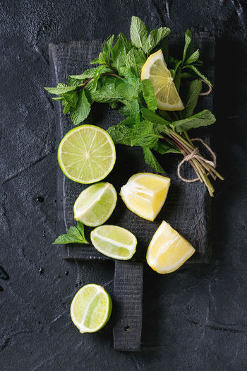 Sliced Lime and lemons with bunch of fresh mint on black wooden chopping board over black textured background. Top view Food And Drink Food Freshness Healthy Eating Directly Above Herb Lemon Leaf SLICE Fruit Plant Part Mint Leaf - Culinary Citrus Fruit Lime Lemonade Ingredients Dark Chopping Board