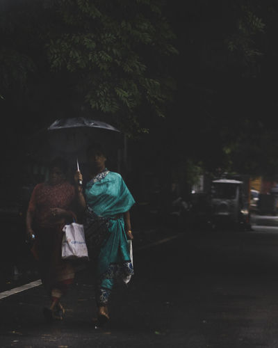 Rear view of people walking on wet street at night