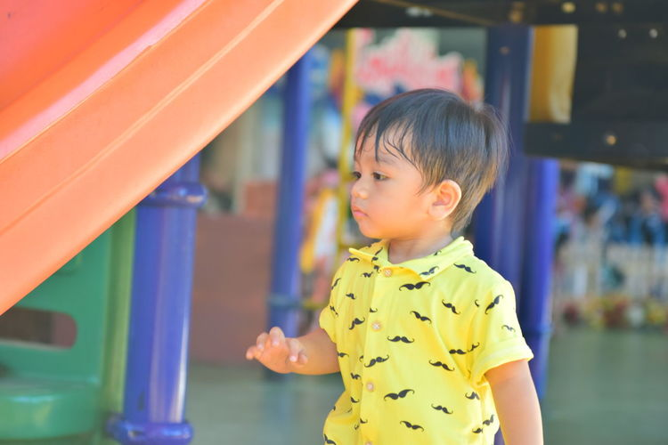 Cute boy looking away while standing by slide in playground