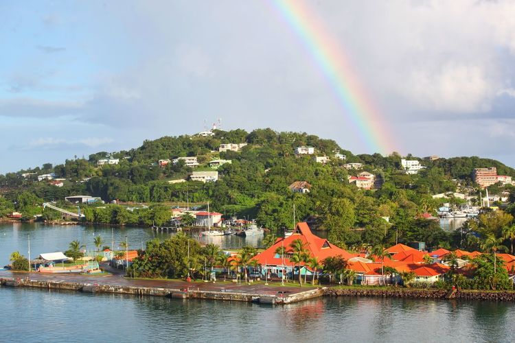 Scenic view of rainbow over river by buildings against sky