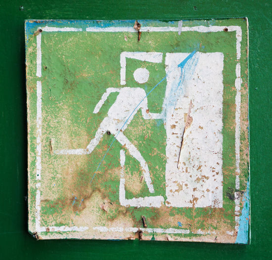Old Square emergency exit symbol on a factory door Safety First! Sign Emergency Exit Evacuation Rescue Run Direction