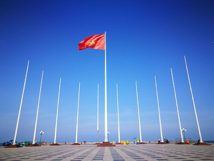 Low angle view of vietnamese flag against blue sky