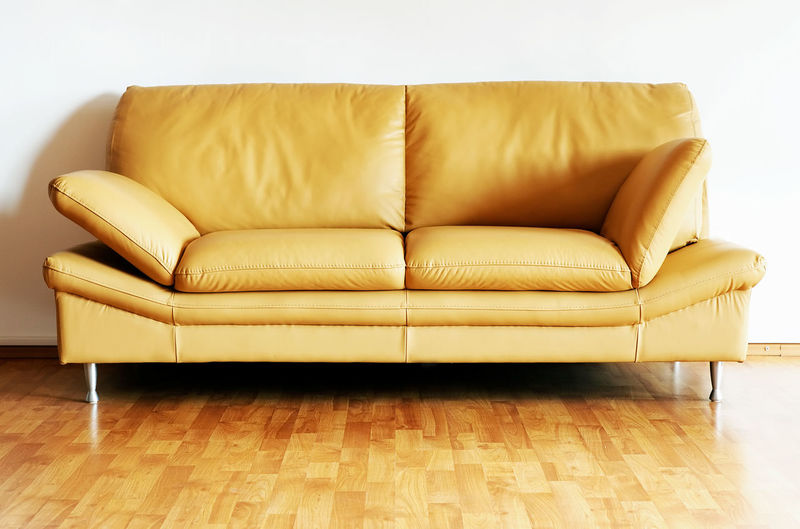 Brown sofa on floor against wall at home