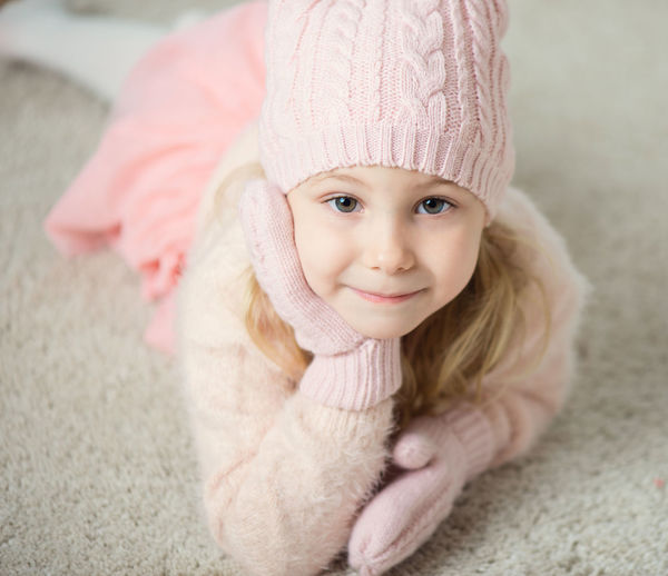 Close-up portrait of cute girl wearing warm clothing at home