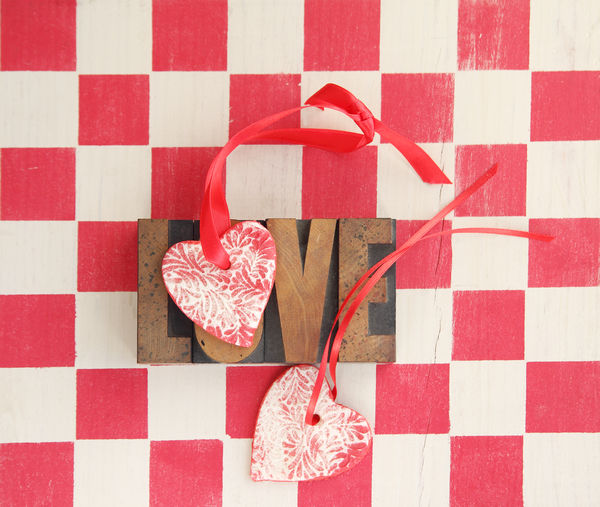 Two handmade heart ornaments with the word 'love' against a red checked background Background Checkerboard Design Geometric Shape Hearts Holiday Indoors  Letters Love Natural Light No People Overhead Pattern Red Ribbons Romantic Salt Dough Ornaments Sentiment Stenciled Textures Type Typography Valentine's Day  Word