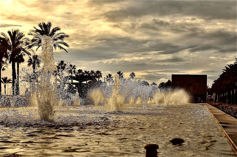Water splashing in fountain against sky at sunset