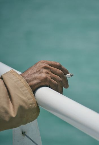 Close-up of man holding cigarette