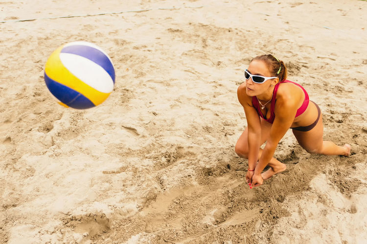 Female Beach Volleyball Player In Action Beach Volleyball Caucasian Girls Court Court Red Activity Ball Beach Bikini Black Day High Angle View Match Net - Sports Equipment One Woman Only Outdoors Sand Sunglasses Sunlight Sunny Day Team Volleyball Women Only Young Woman