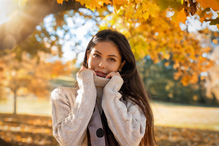Young, attractive woman with a knitted pullover stands in the autumn park Autumn Young Adult One Person Beauty Young Women Beautiful Woman Portrait Tree Looking At Camera Clothing Leisure Activity Hair Women Hairstyle Lifestyles Leaf Scarf Change Nature Outdoors Park Fall Golden October Sun