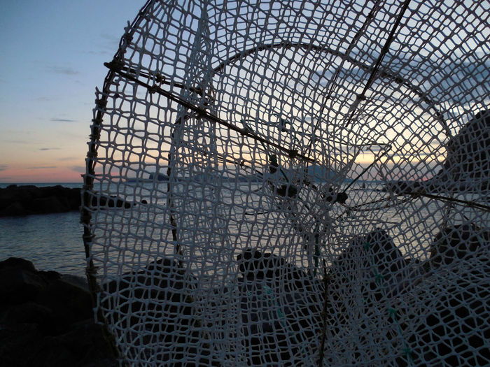 Close-up of fishing net on sea against sky during sunset