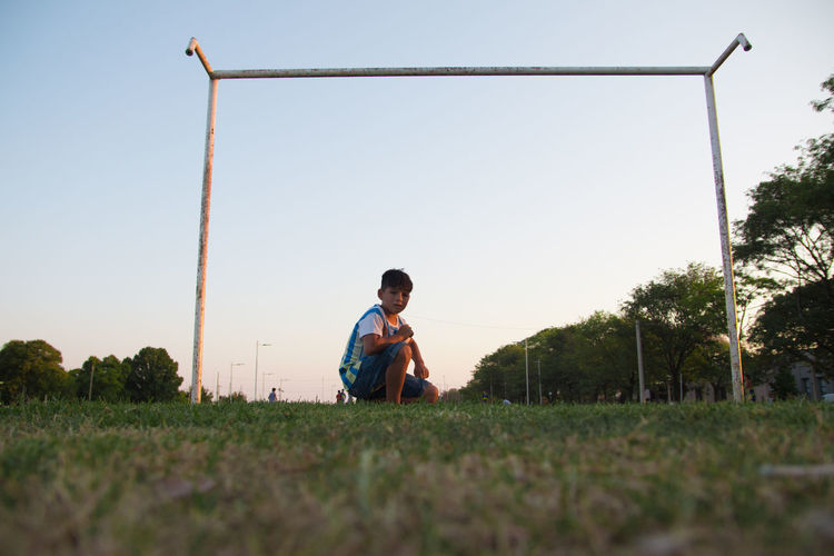 Full length of man sitting on field against clear sky
