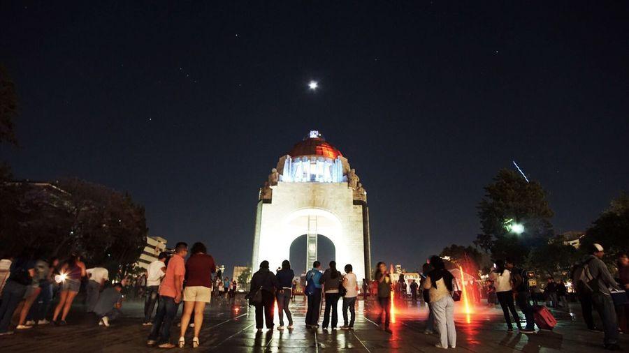 People at illuminated christmas lights in city at night