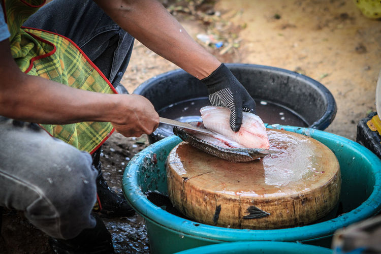 Midsection of man cutting fish in market
