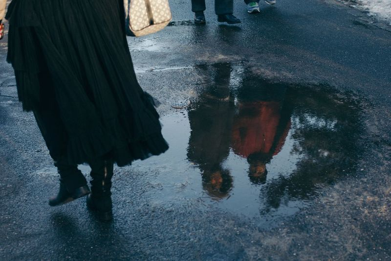People reflecting in puddle on street