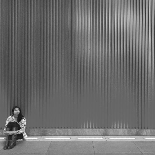 Full length of woman looking away while sitting on footpath by corrugated iron